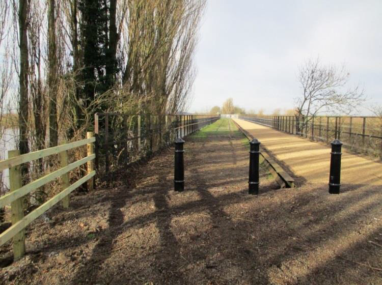 Photo © Sustrans: View west from the Torksey end and shows the new bollards installed to prevent vehicles access and the mesh panels fixed to the trestle viaduct parapets.